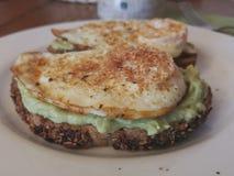 Tostada sana con el aguacate y el huevo frito en la tabla para el desayuno Imagenes de archivo