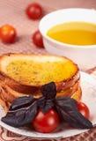 Tostadas, aceite de oliva, hierba de la albahaca y tomates Imagen de archivo libre de regalías