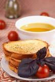 Tostadas, aceite de oliva, hierba de la albahaca y tomates Fotografía de archivo libre de regalías