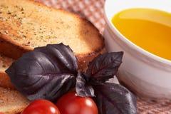 Tostadas, aceite de oliva, hierba de la albahaca y tomates Fotos de archivo