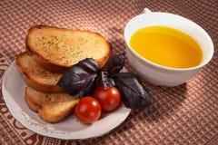 Tostadas, aceite de oliva, hierba de la albahaca y tomates Imagen de archivo