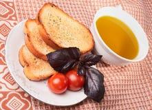 Tostadas, aceite de oliva, hierba de la albahaca y tomates Fotos de archivo libres de regalías