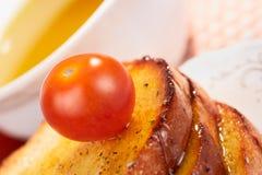 Tostadas, aceite de oliva y tomate de cereza Foto de archivo libre de regalías