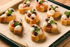 Tostadas cocidas con mozarella, los tomates, las aceitunas y el ajo Fotos de archivo libres de regalías