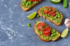 Tostadas con el aguacate, los guisantes verdes y los tomates imagen de archivo libre de regalías