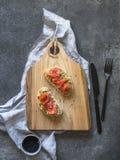 Tostadas con el aguacate y las semillas de sésamo de color salmón y negras saladas en un tablero de madera en un fondo gris Visió foto de archivo libre de regalías