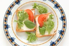 Tostadas con el queso poner crema y el tomate Foto de archivo libre de regalías