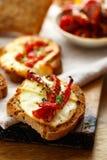 Tostadas con queso ahumado de la leche de ovejas, tomates secados al sol e hierbas Imágenes de archivo libres de regalías