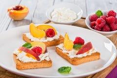 Tostadas de Bruschetta del melocotón de Mascarpone de la frambuesa en plato Fotos de archivo libres de regalías