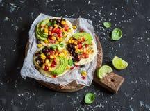 Tostadas de feijão picantes com salsa e abacate do milho em uma placa de corte rústica em um fundo escuro imagem de stock royalty free
