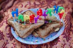 Tostadas de la torta del feliz cumpleaños con las velas foto de archivo