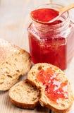 Tostadas del pan del primer con la mermelada de fresa, la cuchara de madera y el tarro con el atasco en la tabla de madera fotografía de archivo libre de regalías