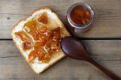 Tostadas deliciosas con los atascos y la cuchara dulces en el fondo de madera, visión superior, espacio de la copia imagen de archivo libre de regalías