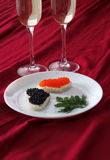 Tostadas en forma de corazón con el caviar rojo y negro y dos vidrios de champán en la placa blanca en la pañería roja Foto de archivo libre de regalías