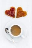 Tostadas en forma del corazón con el atasco de la fruta y la taza de café Imágenes de archivo libres de regalías
