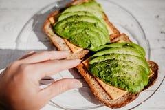 Tostadas enteras del grano con el aguacate, el queso e hierbas Un desayuno delicioso útil fotos de archivo