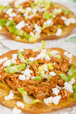 Tostadas. Mexican crispy corn tortilla topped with chicken tinga, lettuce and cotija cheese. Served with pico de gallo, guacamole and crema mexicana Stock Images