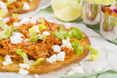 Tostadas. Mexican crispy corn tortilla topped with chicken tinga, lettuce and cotija cheese. Served with pico de gallo, guacamole and crema mexicana Royalty Free Stock Photos