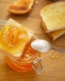 Tostadas y atasco anaranjado en un tarro de cristal imágenes de archivo libres de regalías