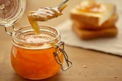 Tostadas y atasco anaranjado en un tarro de cristal foto de archivo