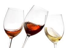 Tostando el vino blanco rojo y del gesto con el chapoteo, alegrías cerca para arriba con el vino aislado Imagen de archivo