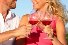 Tostando los vidrios - pares que beben el vino rojo Fotos de archivo libres de regalías