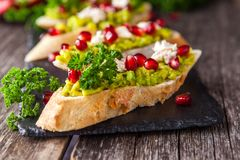 Tosti con l'avocado ed il melograno sulla tavola di legno Fotografia Stock Libera da Diritti
