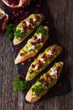 Tosti con l'avocado ed il melograno sulla tavola di legno Immagini Stock