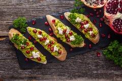 Tosti con l'avocado ed il melograno sulla tavola di legno Immagine Stock Libera da Diritti