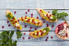 Tosti con l'avocado ed il melograno sulla tavola grigia Fotografia Stock