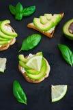Tosti con la cagliata, dell'avocado del formaggio cremoso e la calce su un backgro scuro Fotografie Stock Libere da Diritti