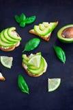 Tosti con la cagliata, dell'avocado del formaggio cremoso e la calce su un backgro scuro Immagine Stock