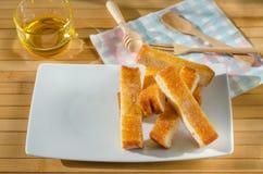 Tosti i bastoni incisi sistemati su un piatto bianco, piatto bianco sopra Fotografia Stock
