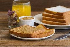Tosti il pane con burro di arachidi casalingo servito con succo d'arancia Fotografie Stock Libere da Diritti