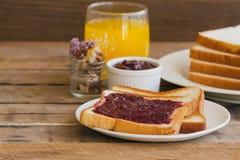 Tosti il pane con l'inceppamento di fragola casalingo servito con juic arancio Immagine Stock Libera da Diritti