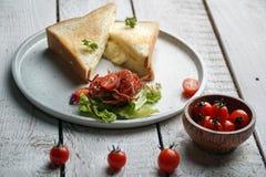 Tosti il panino e l'insalata delle verdure in un piatto bianco sulla tavola di legno bianca immagine stock