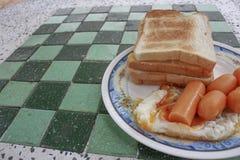 Tosti la prima colazione con le uova fritte e le salsiccie sulla tavola di pietra fotografia stock