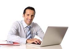 40 tot 50 jaar oude hogere zakenman die aan computer bij bureau werken die zeker en ontspannen kijken Stock Foto