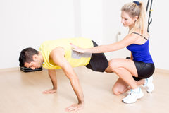 Total body workout. Coach helping with suspension training exercise stock image