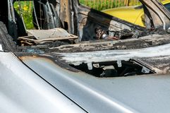 Total damage on new expensive burned car in fire on the parking lot, selective focus.  Royalty Free Stock Image