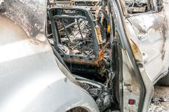 Total damage on new expensive burned car in fire on the parking lot, selective focus close up.  Stock Photo