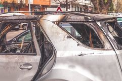 Total damage on new expensive burned car in fire on the parking lot, selective focus close up.  Royalty Free Stock Images