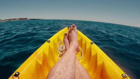 Total lifestyle relax and desconnection concept with men legs in point of view on yellow kayak with blue ocean water around - tour. Ism and travel holiday stock footage