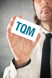 Total Quality Management consultant. Businessman holding TQM card. Selective focus Royalty Free Stock Photo