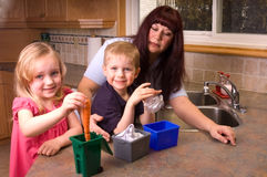 Total Recycling. Concept picture of a mother teaching her two youg children to recycle Royalty Free Stock Images