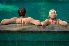 Total relax in a swimming pool. Back view of couple relaxing in a swimming pool on a poolside in tropical resort Stock Images
