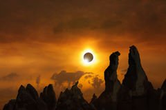 Total solar eclipse. Is amazing mysterious natural phenomenon when Moon passes between planet Earth and Sun. Silhouettes of high rocks on red glowing sky royalty free stock photography