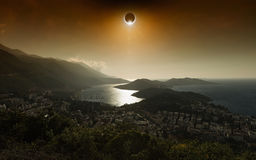 Total solar eclipse in dark red glowing sky above seaside city Royalty Free Stock Photos