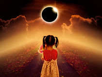 Total solar eclipse glowing above child on pathway with night sk. Amazing scientific natural phenomenon. Total solar eclipse glowing above child on pathway with stock image