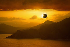 Total solar eclipse, silhouettes of mountains in red glowing sky Stock Images